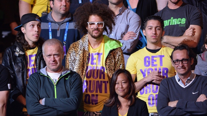 US rapper Redfoo, centre, watches as Victoria Azarenka of Belarus receives her trophy after defeating China's Li Na in the women's final at the Australian Open tennis championship in Melbourne, Australia, Saturday, Jan. 26, 2013. (AP Photo/Andrew Brownbill)