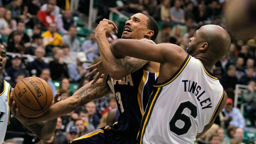 Indiana Pacers guard George Hill, left, is fouled by Utah Jazz guard Jamaal Tinsley (6) whike driving to the basket in the first half during an NBA basketball game on Saturday, Jan. 26, 2013, in Salt Lake City. (AP Photo/Steve C. Wilson)