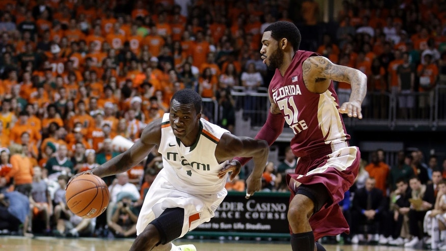 Miami's Durand Scott (1) drives around Florida State's Terry Whisnant II (31) during the first half of an NCAA college basketball game in Coral Gables, Fla., Sunday, Jan. 27, 2013. Miami won 71-47. (AP Photo/Alan Diaz)