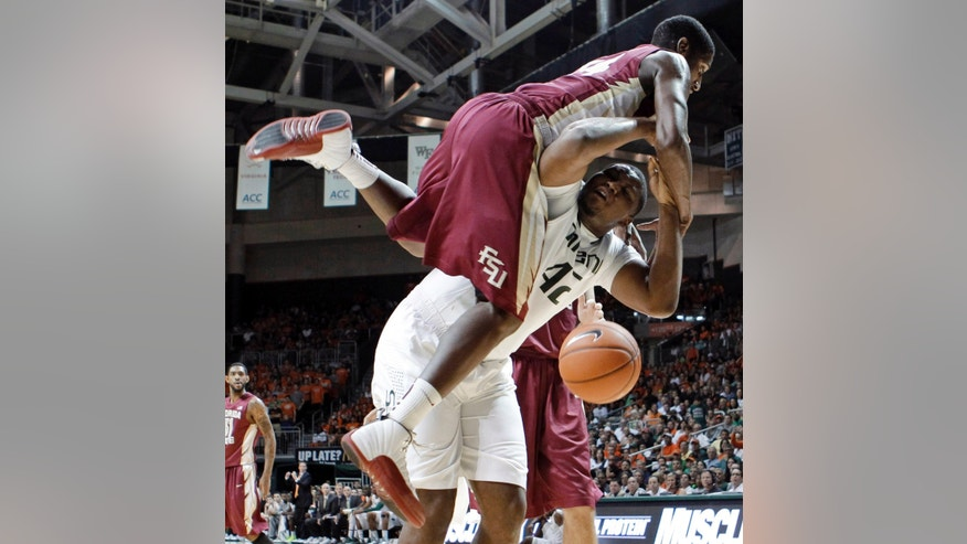Florida State' Robert Gilchrist lands on Miami's Reggie Johnson (42) during the first half of an NCAA college basketball game in Coral Gables, Fla., Sunday, Jan. 27, 2013. Gilchrist was called for a foul. (AP Photo/Alan Diaz)