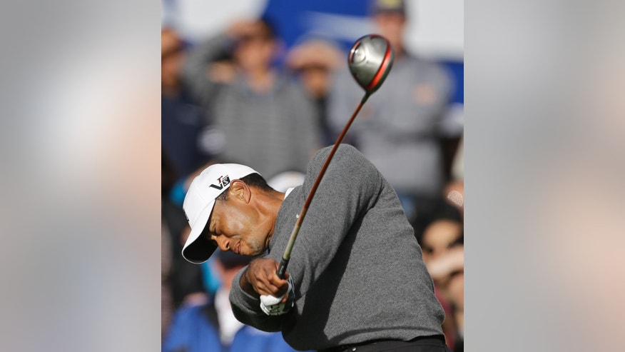 Tiger Woods follows through with his tee shot on the first hole to begin the fourth round of the Farmers Insurance Open golf tournament Sunday, Jan. 27, 2013, in San Diego. The tournament will not conclude until Monday.  (AP Photo/Lenny Ignelzi)