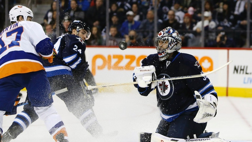 Winnipeg Jets goaltender Al Montoya (35) swipes the puck into the corner as New York Islanders' Matt Martin (17) and Jets' Grant Clitsome (24) battle in front of the net during the first period of their NHL hockey game, Sunday, Jan. 27, 2013, in Winnipeg, Manitoba. (AP Photo/The Canadian Press, Trevor Hagan)