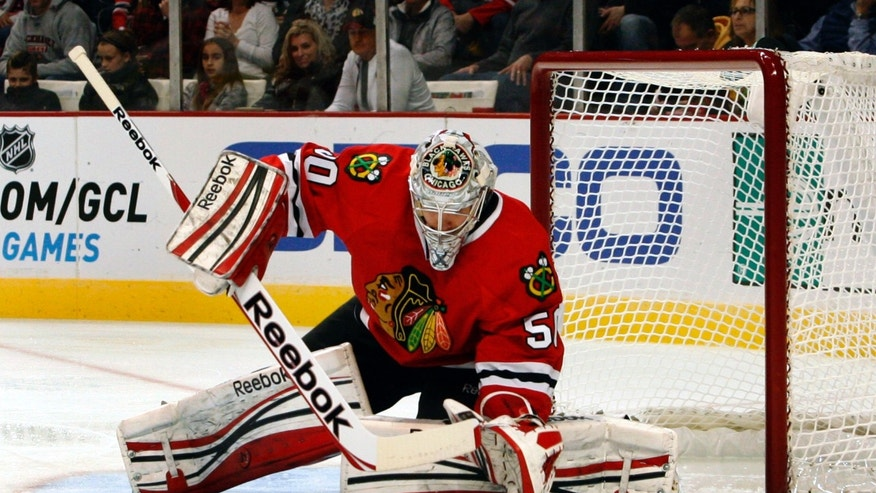Chicago Blackhawks' goalie Corey Crawford stops a shot by the Detroit Red Wings during the first period of an NHL hockey game in Chicago, Sunday, Jan. 27, 2013. (AP Photo/John Smierciak)