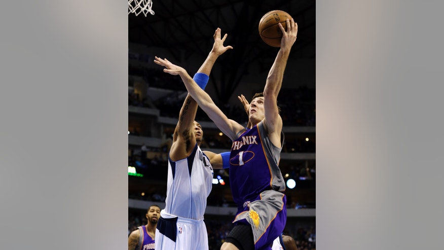 Dallas Mavericks' Shawn Marion (0) defends as Phoenix Suns' Goran Dragic (1), of Slovenia, shoots in the first half of an NBA basketball game, Sunday, Jan. 27, 2013, in Dallas. (AP Photo/Tony Gutierrez)