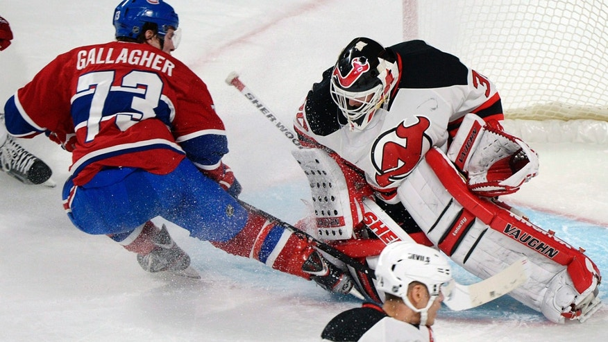 Montreal Canadiens' Brendan Gallagher (73) slides in on New Jersey Devils goaltender Martin Brodeur (30) during the second period of their NHL hockey game, Sunday, Jan. 27, 2013, in Montreal. (AP Photo/The Canadian Press, Graham Hughes)