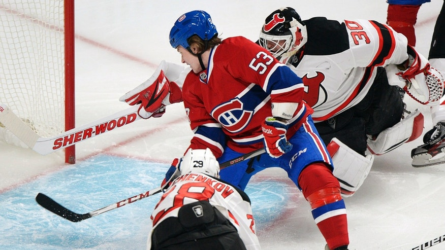 Montreal Canadiens' Ryan White (53) scores against New Jersey Devils goalie Martin Brodeur (30) as Anton Volchenkov looks for a rebound during the first period of their NHL hockey game, Sunday, Jan. 27, 2013, in Montreal. (AP Photo/The Canadian Press, Graham Hughes)
