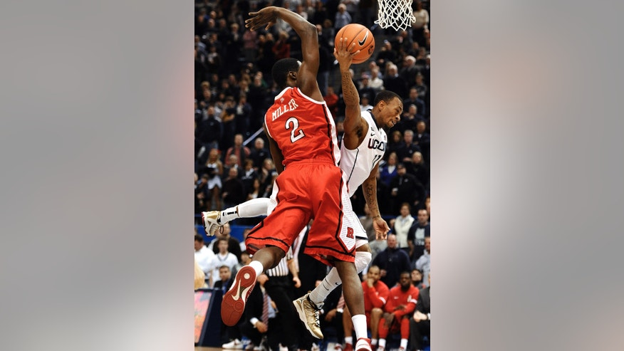 Connecticut's Ryan Boatright, right, is fouled by Rutgers' Dane Miller (2) while driving to the basket during the first half of an NCAA college basketball game in Hartford, Conn., Sunday, Jan. 27, 2013. (AP Photo/Jessica Hill)