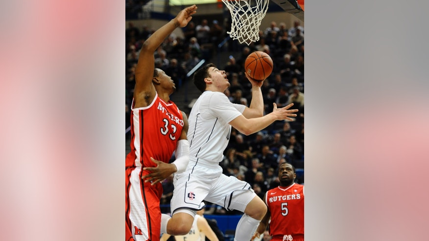 Connecticut's Tyler Olander, center, drives to the basket while guarded by Rutgers' Wally Judge, left, during the first half of an NCAA college basketball game in Hartford, Conn., Sunday, Jan. 27, 2013. (AP Photo/Jessica Hill)