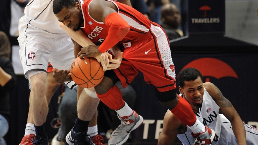 Connecticut's Niels Giffey, left, fouls Rutgers' Eli Carter, center, as Connecticut's Omar Calhoun, right, and Rutgers' Austin Johnson, back, defend during the first half of an NCAA college basketball game in Hartford, Conn., Sunday, Jan. 27, 2013. (AP Photo/Jessica Hill)