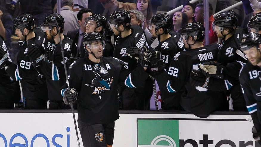 San Jose Sharks center Patrick Marleau (12) high-fives teammates after scoring against the Vancouver Canucks during the second period of an NHL hockey game in San Jose, Calif., Sunday, Jan. 27, 2013. (AP Photo/Tony Avelar)