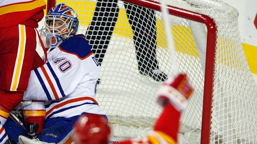 Edmonton Oilers goalie Devan Dubnyk watches as Calgary Flames' Michael Cammalleri celebrates his team's goal during the first period of an NHL hockey game in Calgary, Alberta, Saturday, Jan. 26, 2013. (AP Photo/The Canadian Press, Jeff McIntosh)