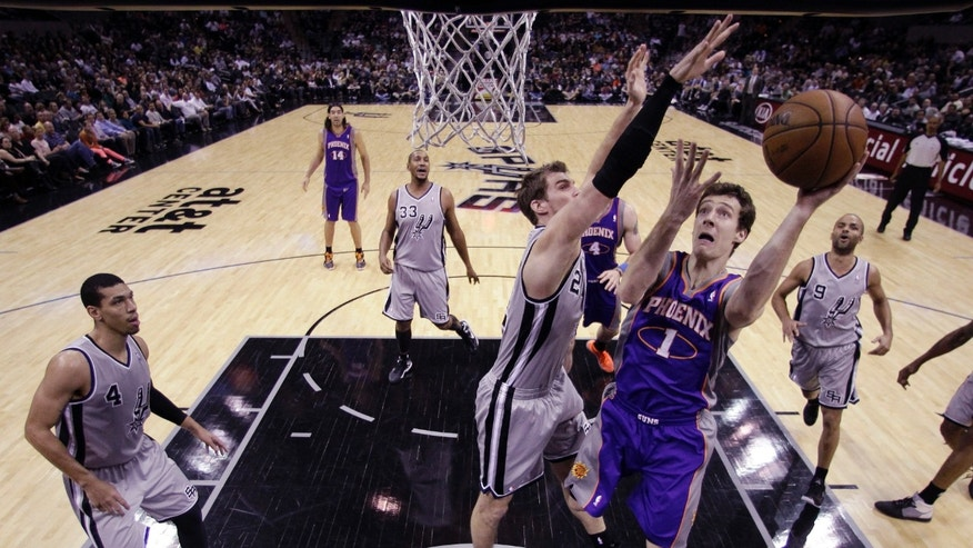 Phoenix Suns' Goran Dragic, 1, of Slovenia, shoots as San Antonio Spurs' Tiago Splitter (22), of Brazil, defends during the first quarter of an NBA basketball game, Saturday, Jan. 26, 2013, in San Antonio, Texas. (AP Photo/Eric Gay)