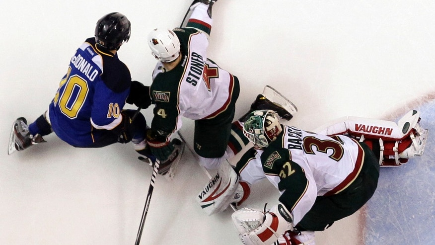 Minnesota Wild's Clayton Stoner, center, uses his foot to keep the puck away from St. Louis Blues' Andy McDonald, left, as Wild goalie Niklas Backstrom, of Finland, watches during the second period of an NHL hockey game Sunday, Jan. 27, 2013, in St. Louis. (AP Photo/Jeff Roberson)