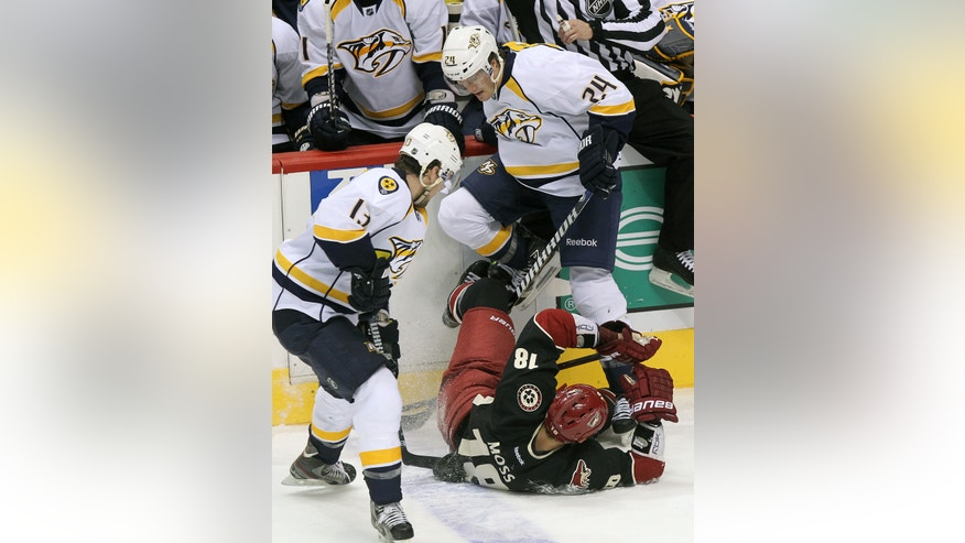 Nashville Predators right wing Matt Halischuk (24) and Phoenix Coyotes left wing David Moss (18) battle for the puck in the second period during an NHL hockey game on Monday, Jan. 28, 2013, in Glendale, Ariz. (AP Photo/Rick Scuteri)