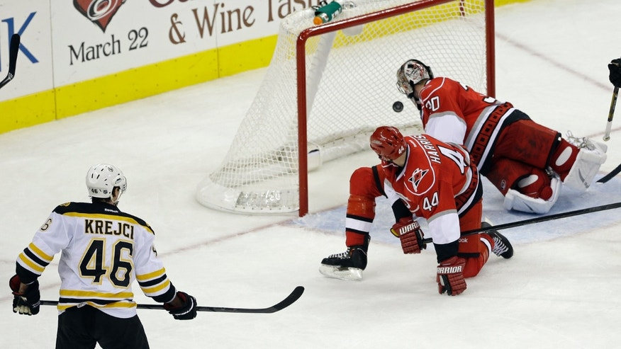 Boston Bruins' David Krejci (46), of the Czech Republic, watches his game winning goal go past Carolina Hurricanes goalie Cam Ward (30) as Hurricanes' Jay Harrison (44) looks back during the third period of an NHL hockey game in Raleigh, N.C., Monday, Jan. 28, 2013.  Boston won 5-3. (AP Photo/Gerry Broome)