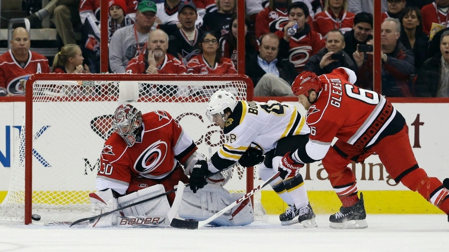 Carolina Hurricanes goalie Cam Ward (30) deflects a shot by Boston Bruins' Chris Bourque (48) as Hurricanes' Tim Gleason (6) defends during the second period of an NHL hockey game in Raleigh, N.C., Monday, Jan. 28, 2013. (AP Photo/Gerry Broome)