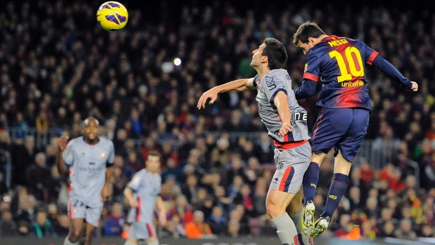 Barcelona's Lionel Messi, from Argentina, right,  vies for the ball with Osasuna's Marc Bertran during their Spanish League soccer match at Camp Nou stadium in Barcelona, Spain, Sunday, Jan. 27, 2013. Barcelona won the match 5-1. (AP Photo/Alvaro Barrientos)