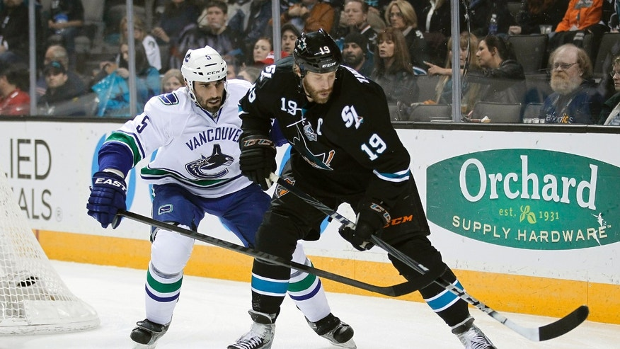 San Jose Sharks center Joe Thornton (19) works for the puck against Vancouver Canucks defenseman Jason Garrison (5) during the first period of an NHL hockey game in San Jose, Calif., Sunday, Jan. 27, 2013. (AP Photo/Tony Avelar)
