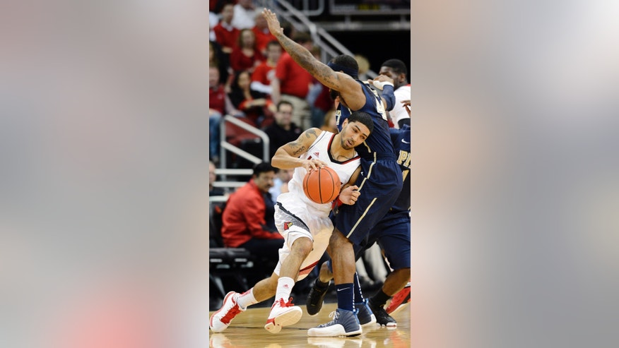 Louisville's Peyton Siva, front, tries to fight his way around the defensive screen of Pittsburgh's J.J. Moore during the first half of their NCAA college basketball game, Monday, Jan. 28, 2013, in Louisville, Ky. (AP Photo/Timothy D. Easley)