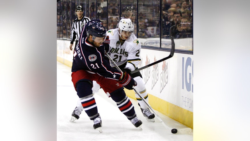 Columbus Blue Jackets' James Wisniewski (21) battles for the puck with Dallas Stars' Loui Eriksson (21), of Sweden, in the first period of their NHL hockey game, Monday, Jan. 28, 2013, in Columbus, Ohio. (AP Photo/Mike Munden)