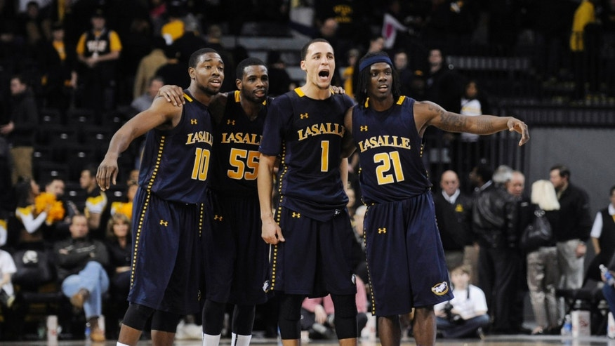 La Salle's Sam Mills (10), Ramon Galloway (55) D.J. Peterson (1) and Tyrone Garland (21) watch as Tyreek Duren shoots a free throw late in La Salle's 69-61 win over Virginia Commonwealth in an NCAA college basketball game Saturday, Jan. 26, 2013, in Richmond, Va. (AP Photo/Clement Britt)