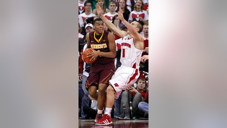 Minnesota's Andre Hollis fouls Wisconsin's Ben Brust, right, in the final seconds of their NCAA college basketball game, Saturday, Jan. 26, 2013, in Madison, Wis. Wisconsin won 45-44. (AP Photo/Andy Manis)
