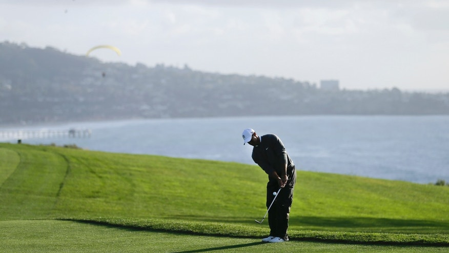 Tiger Woods chips in for birdie on the fourth hole during the fourth round of the Farmers Insurance Open golf tournament at the Torrey Pines Golf Course on Sunday, Jan. 27, 2013, in San Diego. (AP Photo/Gregory Bull)