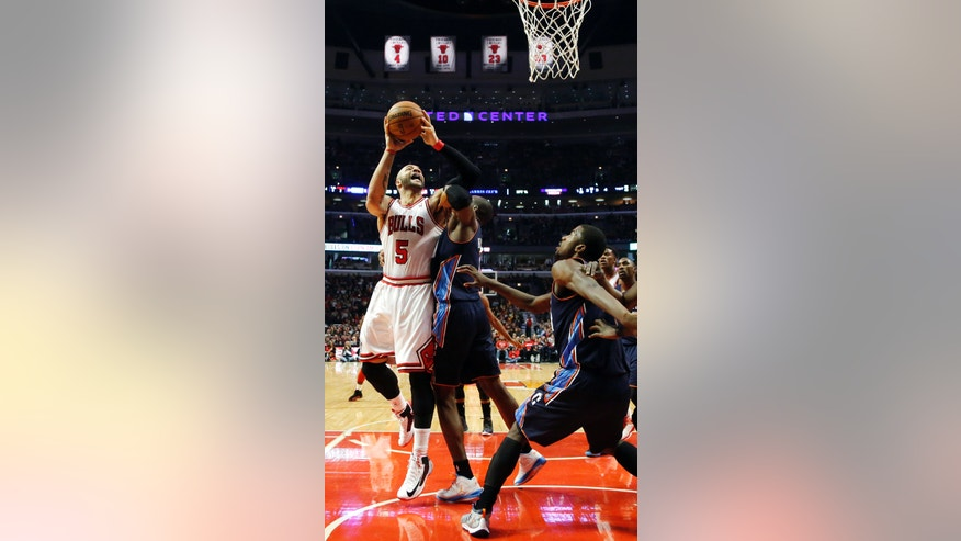 Chicago Bulls forward Carlos Boozer (5) shoots over Charlotte Bobcats forward Bismack Biyombo during the first half of an NBA basketball game, Monday, Jan. 28, 2013, in Chicago. (AP Photo/Charles Rex Arbogast)