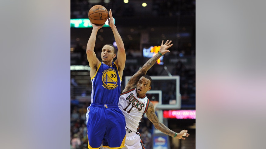 Golden State Warriors' Stephen Curry (30) shoots a three-point basket as Milwaukee Bucks' Monta Ellis (11) defends during the first half of an NBA basketball game on Saturday, Jan. 26, 2013, in Milwaukee. (AP Photo/Jim Prisching)