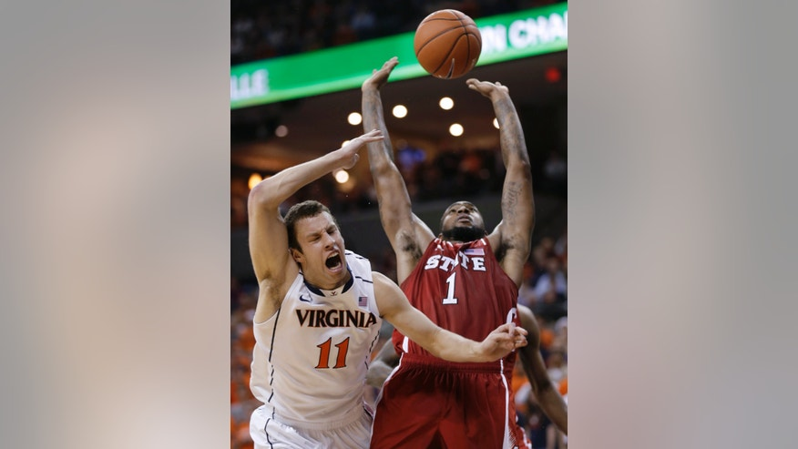 Virginia forward Evan Nolte (11) reacts to a collision with North Carolina State forward Richard Howell (1) during the second half of an NCAA college basketball game   Tuesday, Jan. 29, 2013, in Charlottesville, Va. Virginia won 58-55. (AP Photo/Steve Helber)