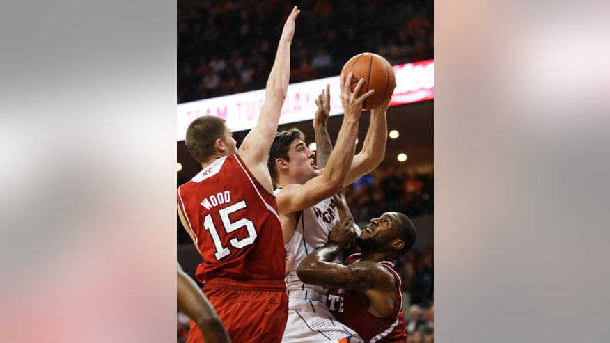 Virginia guard Joe Harris (12) takes a shot at North Carolina State forwards Scott Wood (15) and Richard Howell, right, defend during the second half of an NCAA college basketball game Tuesday, Jan. 29, 2013, in Charlottesville, Va. Virginia won 58-55. (AP Photo/Steve Helber)