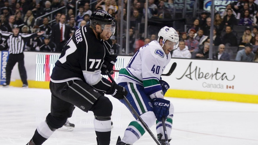 Los Angeles Kings center Jeff Carter, left,  battles Vancouver Canucks center Maxim Lapierre, right, for the puck during the first period of an NHL Hockey game in Los Angeles, Monday, Jan. 28, 2013. (AP Photo/Chris Carlson)