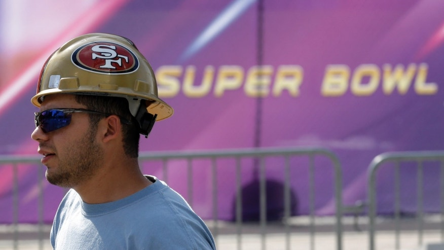 Jan. 27, 2013: A worker in a San Francisco 49ers hard hat walks outside of the Mercedes-Benz Superdome as preparations take place for the NFL Super Bowl XLVII football game.