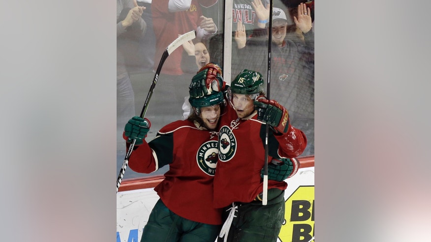 Minnesota Wild's Dany Heatley, right, congratulates Tom Gilbert on his goal off Columbus Blue Jackets goalie Steve Mason in the first period of an NHL hockey game Tuesday, Jan. 29, 2013 in Saint Paul, Minn. (AP Photo/Jim Mone)