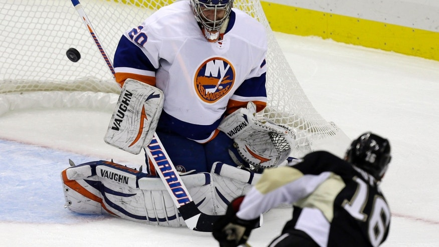 New York Islanders goalie Evgeni Nabokov (20) blocks a shot by Pittsburgh Penguins center Brandon Sutter (16) during the first period of an NHL hockey game in Pittsburgh Tuesday, Jan. 29, 2013. (AP Photo/Gene J. Puskar)