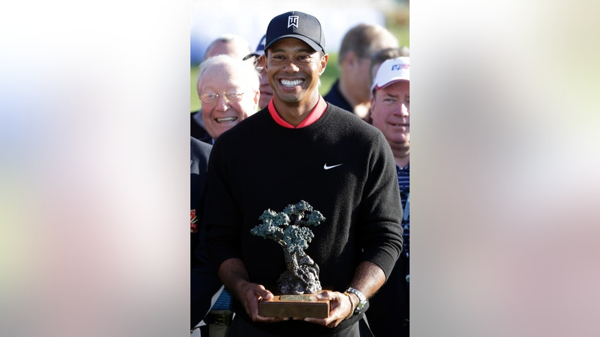 Tiger Woods poses with the trophy after winning the Farmers Insurance Open golf tournament at the Torrey Pines Golf Course, Monday, Jan. 28, 2013, in San Diego. Woods closed with an even-par 72 for a four-shot victory. (AP Photo/Gregory Bull)