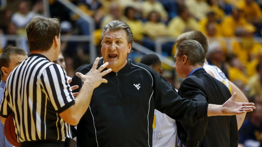 West Virginia' coach Bob Huggins argues with an official during the first half of an NCAA college basketball game in Morgantown, W.Va., on Monday, Jan. 28, 2013.  (AP Photo/David Smith)