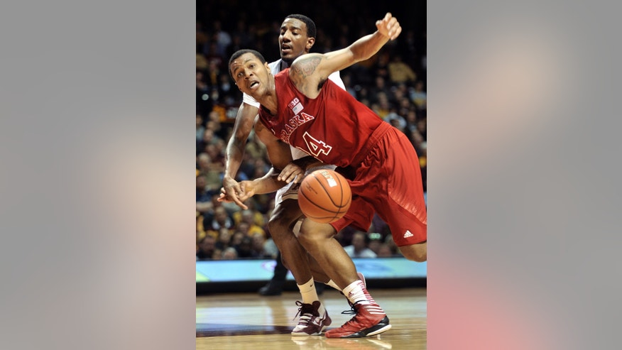 Minnesota's Austin Hollins, rear, bats the ball away from Nebraska's Dylan Talley, front, as Talley attempts to drive the lane during the first half of an NCAA college basketball game, Tuesday, Jan. 29, 2013, in Minneapolis. (AP Photo/Tom Olmscheid)