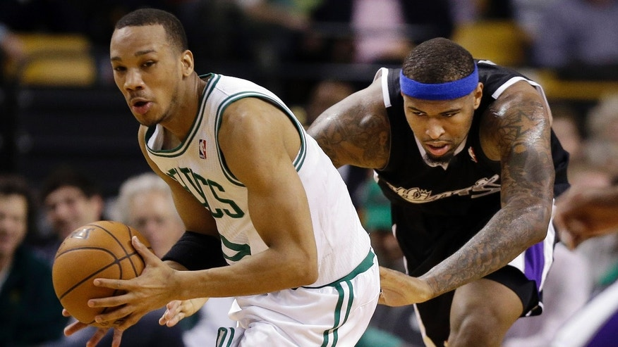 Boston Celtics guard Avery Bradley (0) comes up with a loose ball in front of Sacramento Kings center DeMarcus Cousins (15) during the first half of an NBA basketball game in Boston, Wednesday, Jan. 30, 2013. (AP Photo/Elise Amendola)