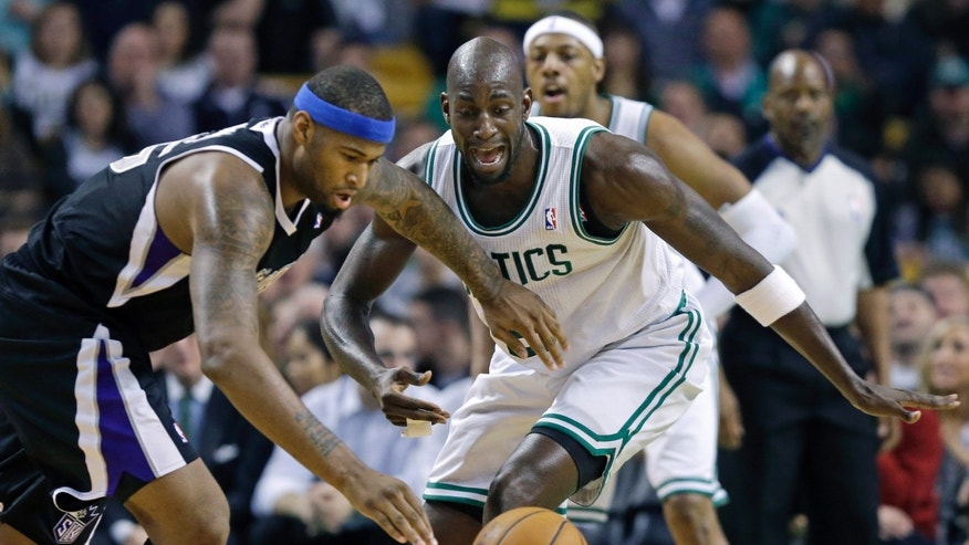 Sacramento Kings center DeMarcus Cousins (15) controls the ball as Boston Celtics power forward Kevin Garnett, right, defends during the first half of an NBA basketball game in Boston, Wednesday, Jan. 30, 2013. (AP Photo/Elise Amendola)
