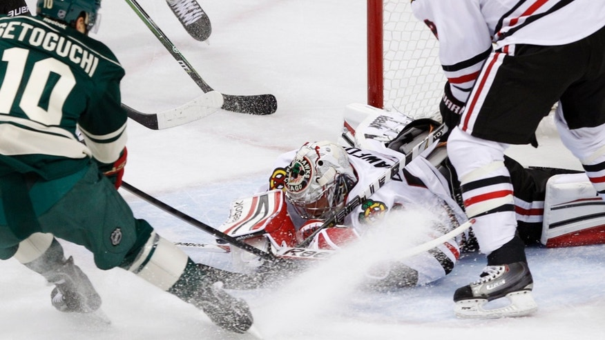 Chicago Blackhawks goalie Corey Crawford (50) makes a save against Minnesota Wild right wing Devin Setoguchi (10) during the first period of an NHL hockey game Wednesday, Jan. 30, 2013, in St. Paul, Minn. (AP Photo/Genevieve Ross)