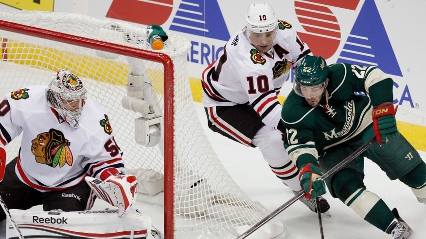 Minnesota Wild right wing Cal Clutterbuck (22) attempts to score on Chicago Blackhawks goalie Corey Crawford (50) as Blackhawks center Patrick Sharp (10) defends during the first period of an NHL hockey game Wednesday, Jan. 30, 2013, in St. Paul, Minn. (AP Photo/Genevieve Ross)