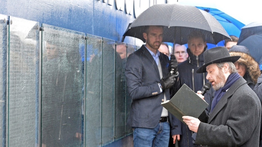 A rabbi prays in front of players Christoph Metzelder and Benedikt Hoewedes, from left, at a new memorial plaque at the stadium of Bundesliga soccer club FC Schalke 04, dedicated to the forgotten Jewish club members who were persecuted and murdered during the holocaust, Gelsenkirchen, western Germany, Wednesday, Jan. 30, 2012. Schalke was the most successful club in Nazi Germany and won the championship 6 times between 1934 and 1942. (AP Photo/Martin Meissner)