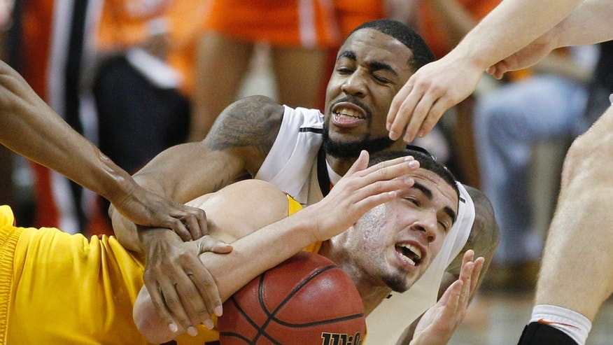 Oklahoma State forward Michael Cobbins, rear, and Iowa State forward Georges Niang, front, fight for control of the ball in the first half of an NCAA college basketball game in Stillwater, Okla., Wednesday, Jan. 30, 2013. (AP Photo/Sue Ogrocki)