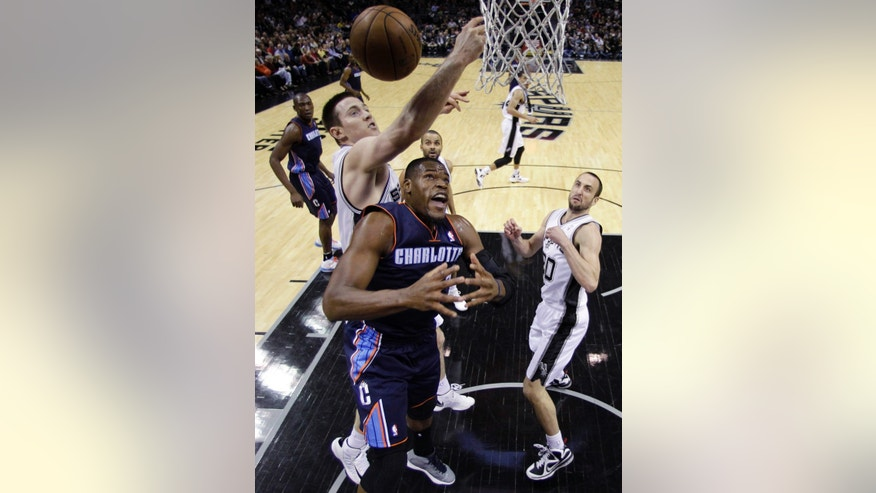 San Antonio Spurs' Aron Baynes, left, reaches over Charlotte Bobcats' Bismack Biyombo, center, for a rebound during the first half of an NBA basketball game, Wednesday, Jan. 30, 2013, in San Antonio. San Antonio Spurs' Manu Ginobili, right, of Argentina, watches. (AP Photo/Eric Gay)