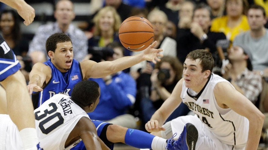 Duke's Seth Curry, top left, loses the ball as Wake Forest's Tyler Cavanaugh, right, and Travis McKie, left, defend during the first half of an NCAA college basketball game in Winston-Salem, N.C., Wednesday, Jan. 30, 2013. (AP Photo/Chuck Burton)