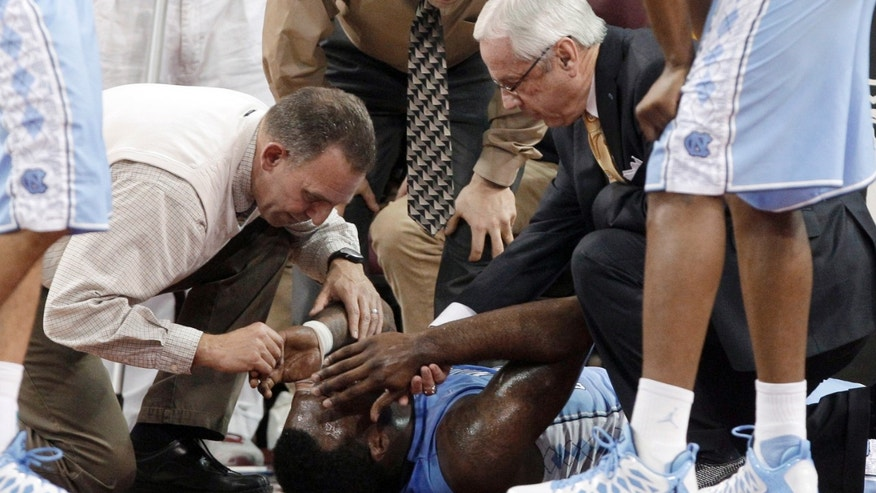 North Carolina's P.J. Hairston is attended to by a trainer and North Carolina coach Roy Williams after an injury during the first half of an NCAA college basketball game against Boston College in Boston, Tuesday, Jan. 29, 2013. (AP Photo/Mary Schwalm)