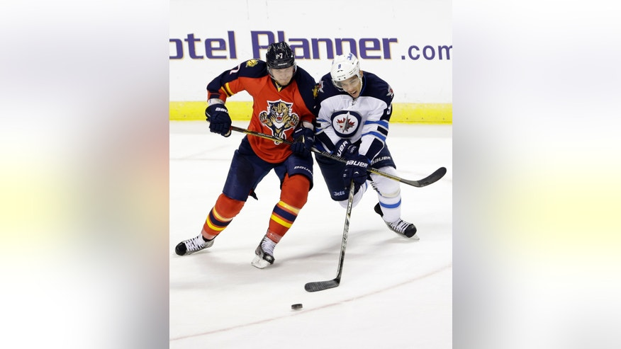 Florida Panthers defenseman Dmitry Kulikov, left, of Russia, and Winnipeg Jets left wing Evander Kane, of Canada, battle for the puck during the second period of an NHL hockey game, Thursday, Jan. 31, 2013, in Sunrise, Fla. (AP Photo/Wilfredo Lee)