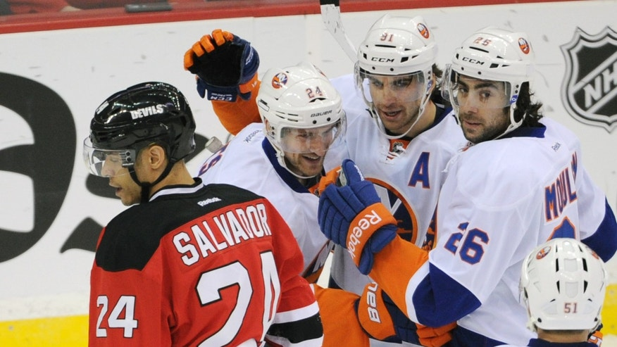 New York Islanders' Brad Boyes (24) and Eric Boulton (36) celebrate with John Tavares after Tavares scored a goal, while New Jersey Devils' Bryce Salvador skates away during the first period of an NHL hockey game Thursday, Jan. 31, 2013, in Newark, N.J. (AP Photo/Bill Kostroun)