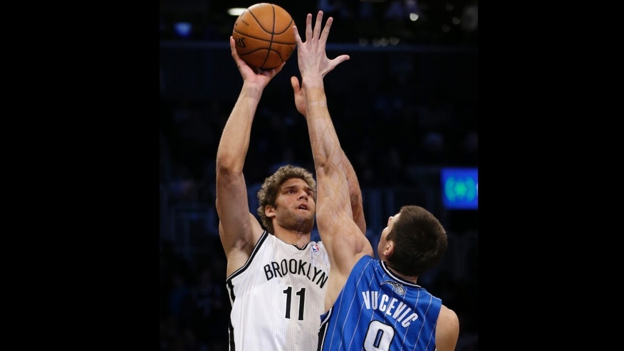 Brooklyn Nets center Brook Lopez (11) shoots over the defense of Orlando Magic center Nikola Vucevic (9) in the first half of their NBA basketball game at the Barclays Center, Monday, Jan. 28, 2013 in New York.  Lopez scored 16 points in the Nets 97-77 victory over the Magic. (AP Photo/Kathy Willens)